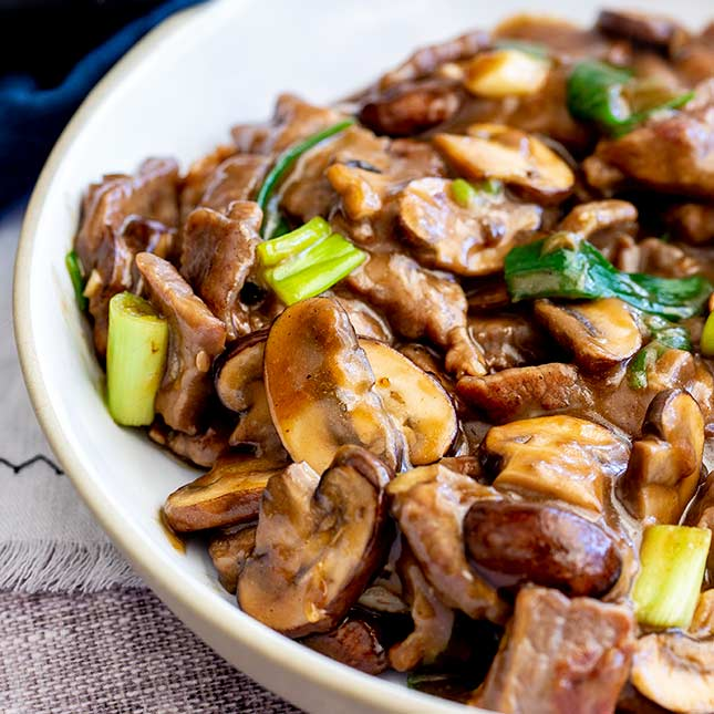 sliced mushrooms and beef in a white bowl with a brown sauce