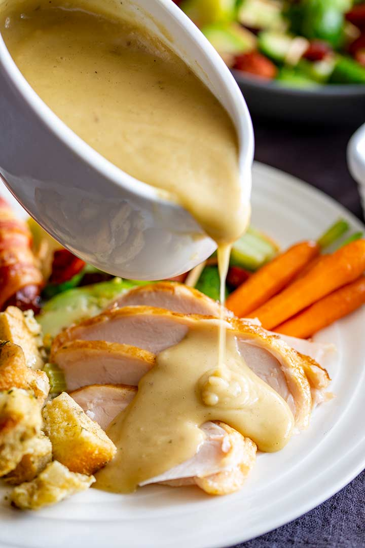turkey gravy being poured from a white gravy boat onto slices of turkey