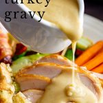 gravy being poured over a roast turkey dinner with text at the top