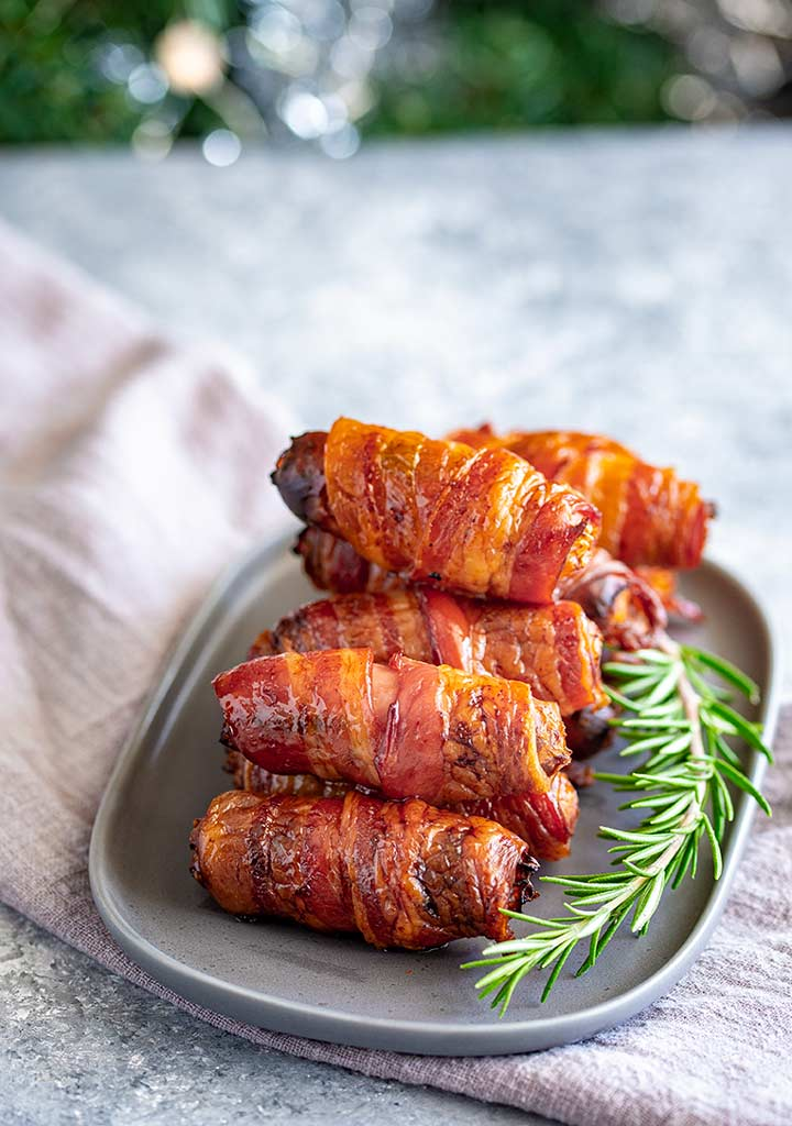 a grey oval plate piled with sausages wrapped in bacon with a rosemary sprig and a linen napkin
