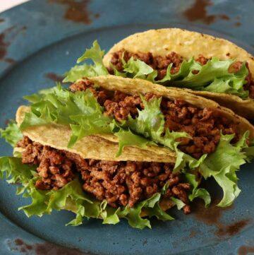 close up on 3 hard beef tacos on a blue plate
