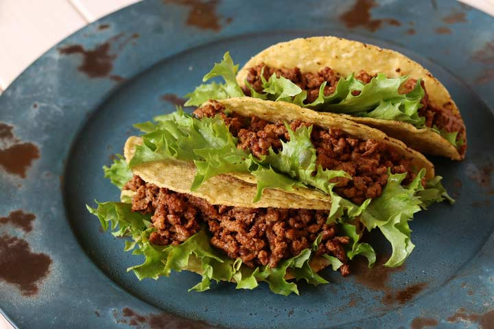 3 corn tacos on a rustic metal plate filled with Mexican ground beef