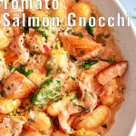 overhead close up of salmon gnocchi with text at the top