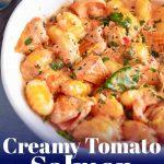 white bowl of creamy tomato salmon gnocchi with text at the bottom