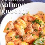 white bowl of creamy tomato salmon gnocchi with text at the top