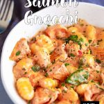 white bowl of creamy tomato salmon gnocchi with text at the top and bottom