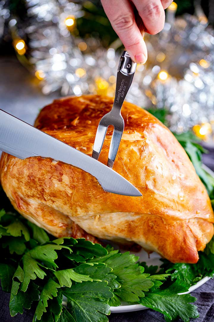 a turkey crown breast being carved with Christmas decorations in the background