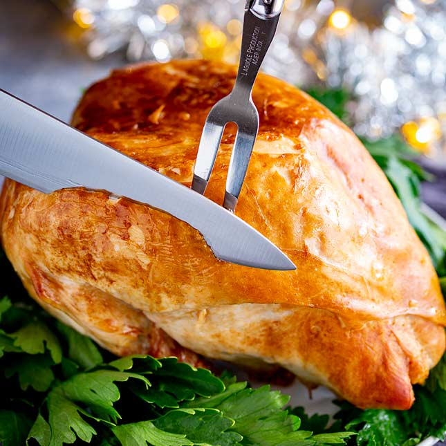 a silver knife carving a Christmas Turkey Crown