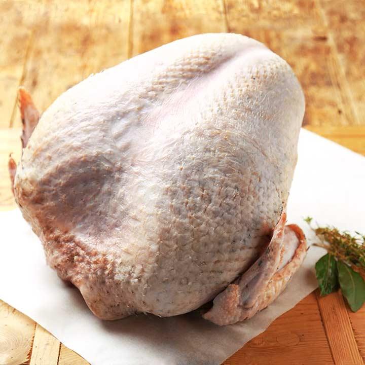 a raw bone in turkey breast sitting on a wooden board