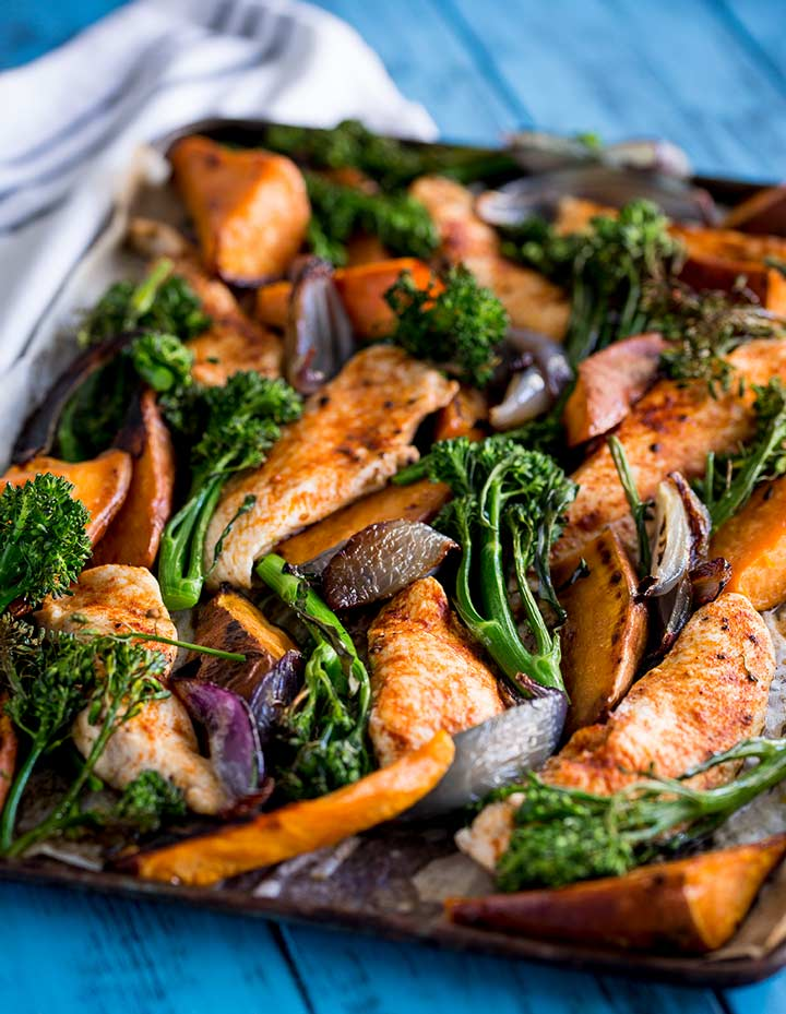 a sheet pan of chicken, sweet potato and broccoli on a blue table