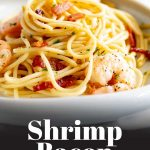 a white plate of pasta with shrimp on top and text at the bottom