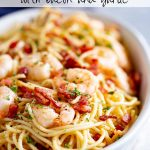 an oval dish of pasta with shrimp on top and text at the top