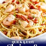 an oval dish of pasta with shrimp on top and text at the bottom