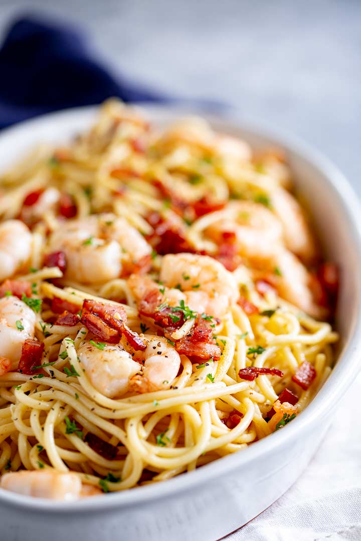 a white oval dish filled with spaghetti, shrimp and bacon