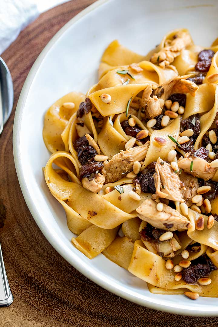 close up on the thick pasta noodles, shredded chicken, raisins and pine nuts in a white bowl