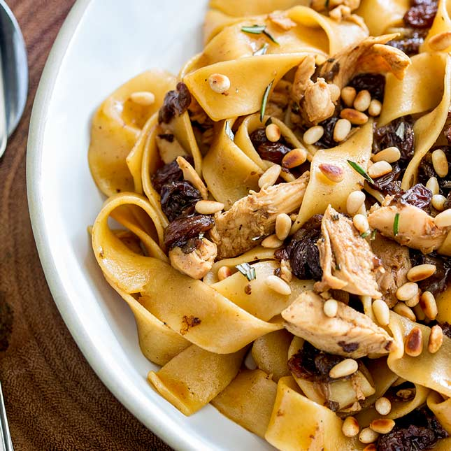 super close up on thick pasta noodles with chicken, raisins and pine nuts