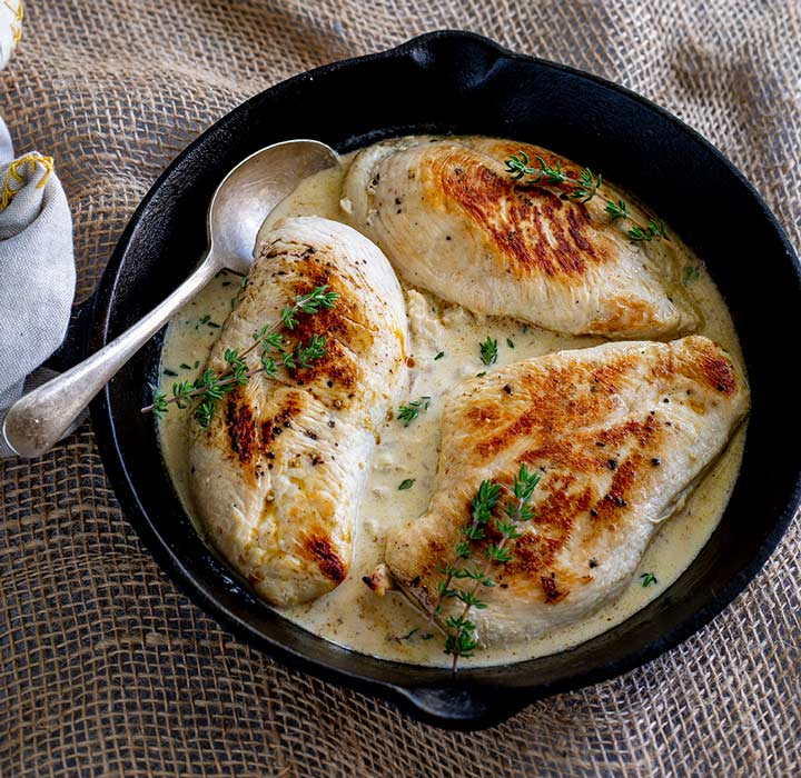 overhead - 3 chicken breast and white wine sauce in a cast iron skillet
