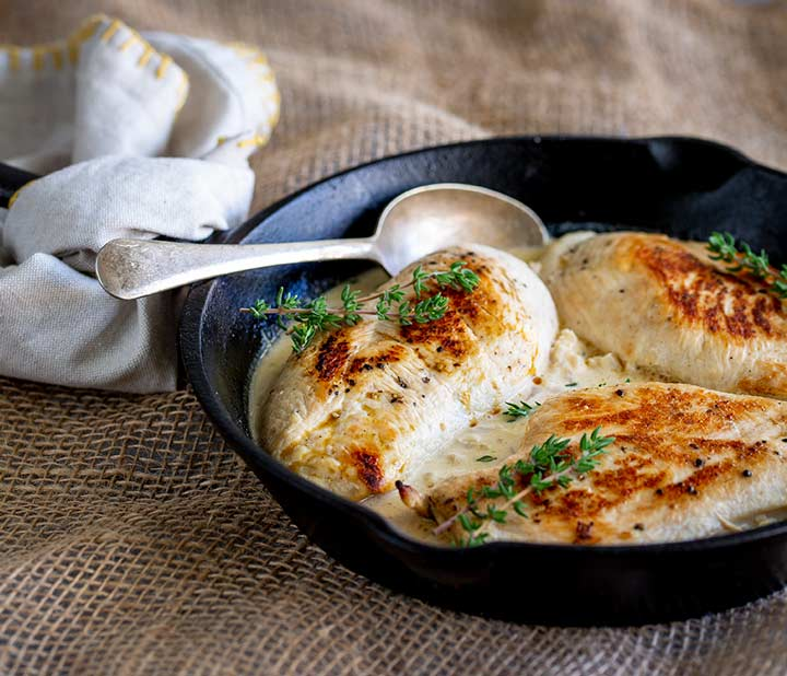 a cast iron skillet on a rustic table with creamy chicken breasts