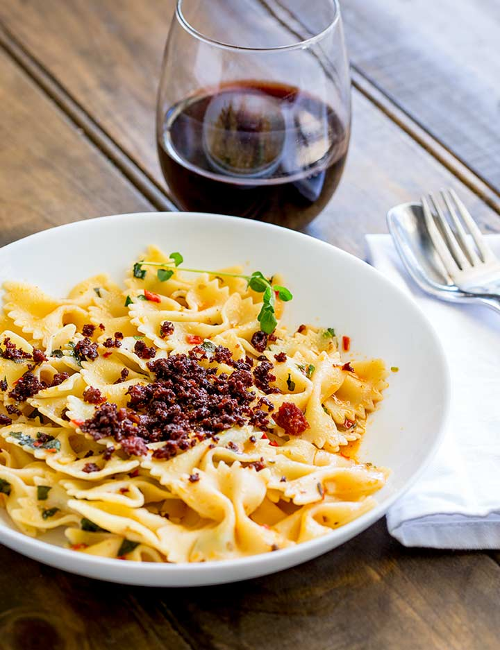 wooden table with a white bowl of chorizo pasta and a glass of red wine.