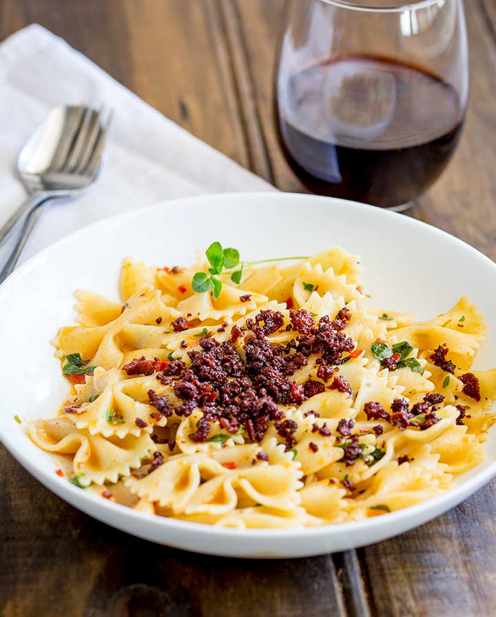 wooden table with a bowl of pasta, white napkin and a glass of red wine