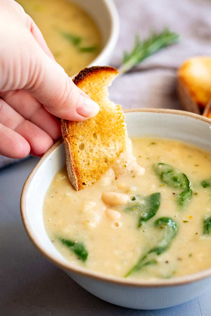 a piece of bread being dipped into creamy bean soup