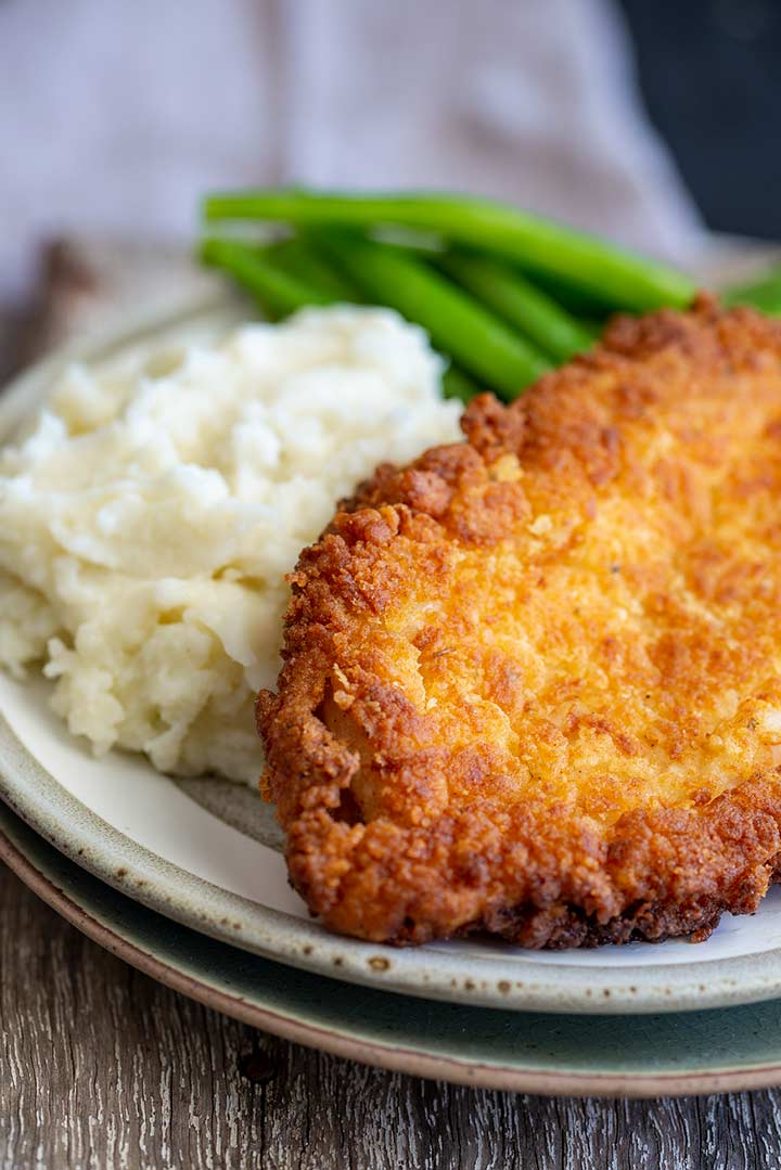 fried chicken with mash and green beans on a grey plate