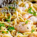 Close up on the shrimp in a bowl of pasta with text at the top
