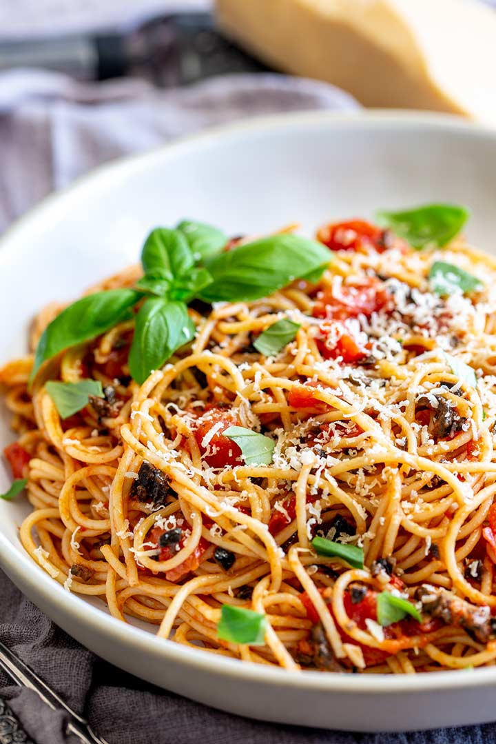 large bowl of spaghetti with tomatoes and olive with parmesan in the background
