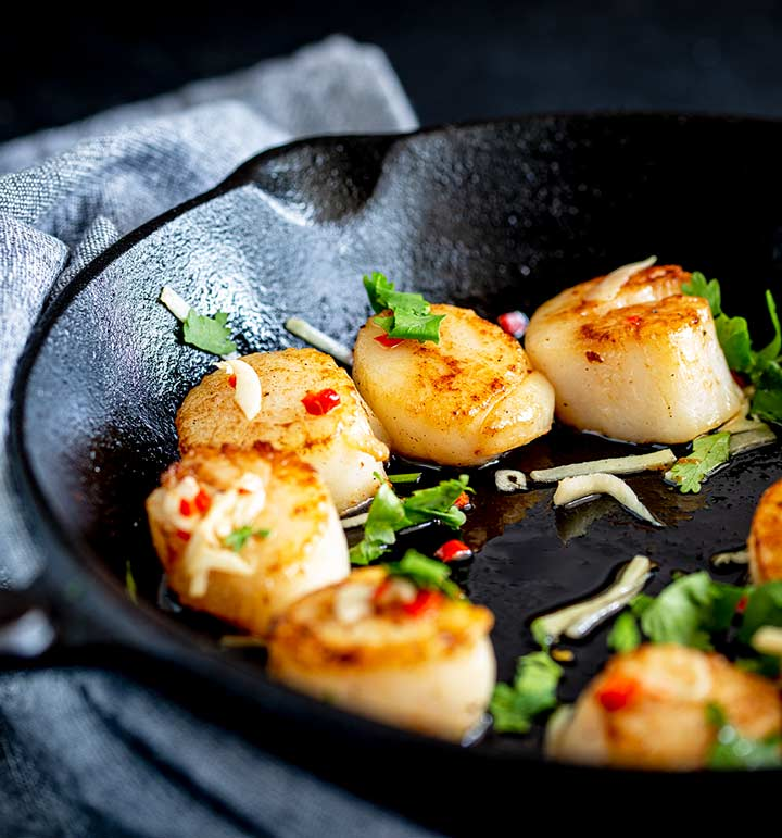 a cast iron skillet with scallops and a Thai dressing on a grey napkin