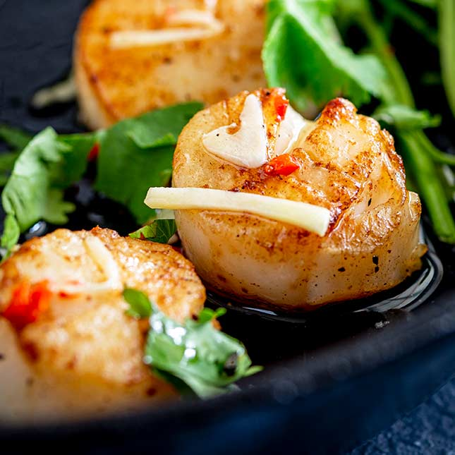 Extreme close up on a seared scallop with Thai sauce