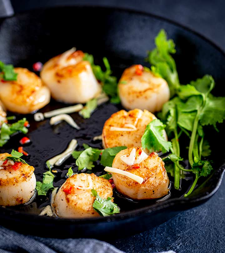 a cast iron pan on a black table with seared scallops and a Thai dressing.