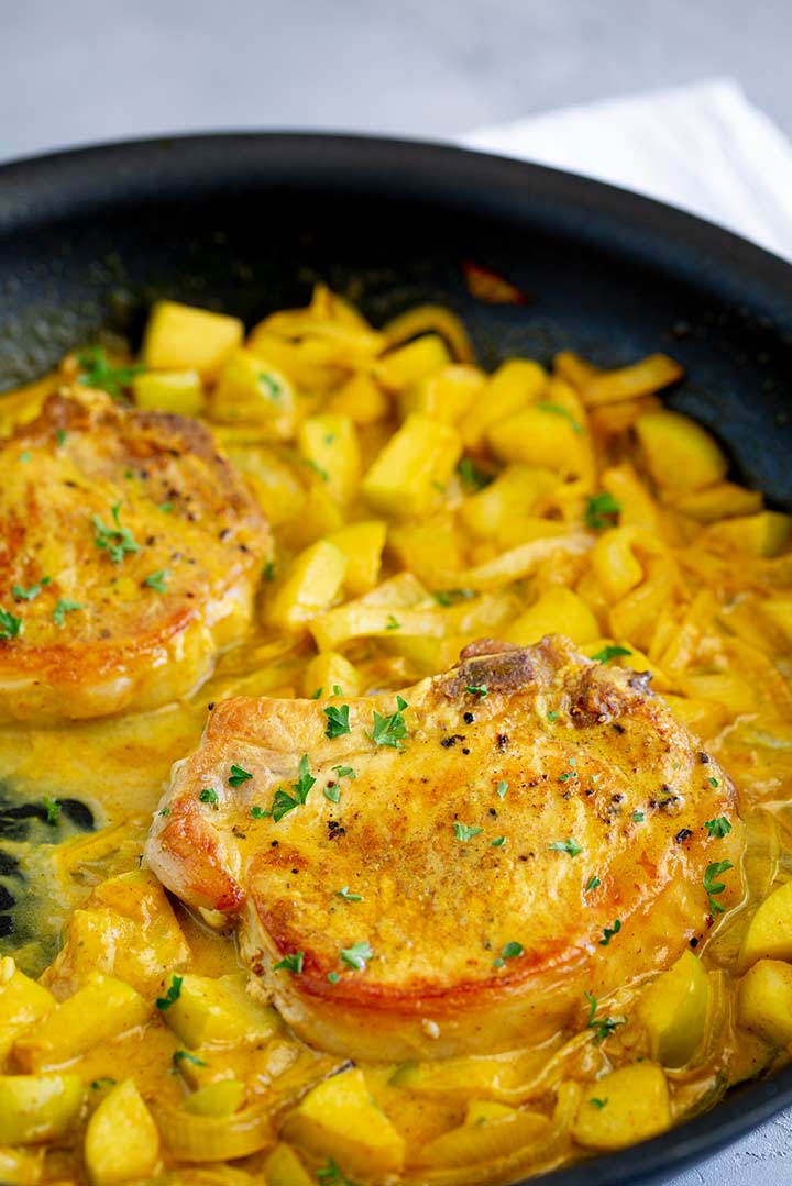 two pork chops in curry sauce in a black skillet