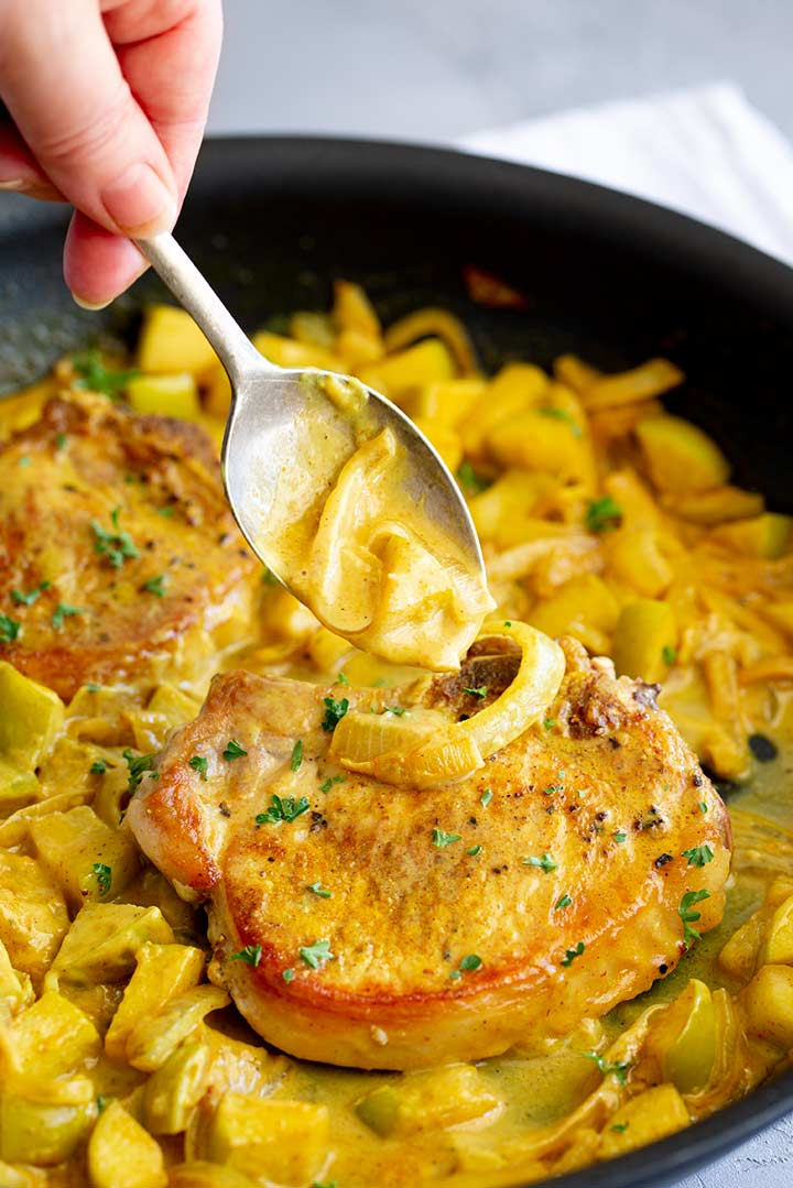 curry sauce being spooned over pork chops in a black skillet