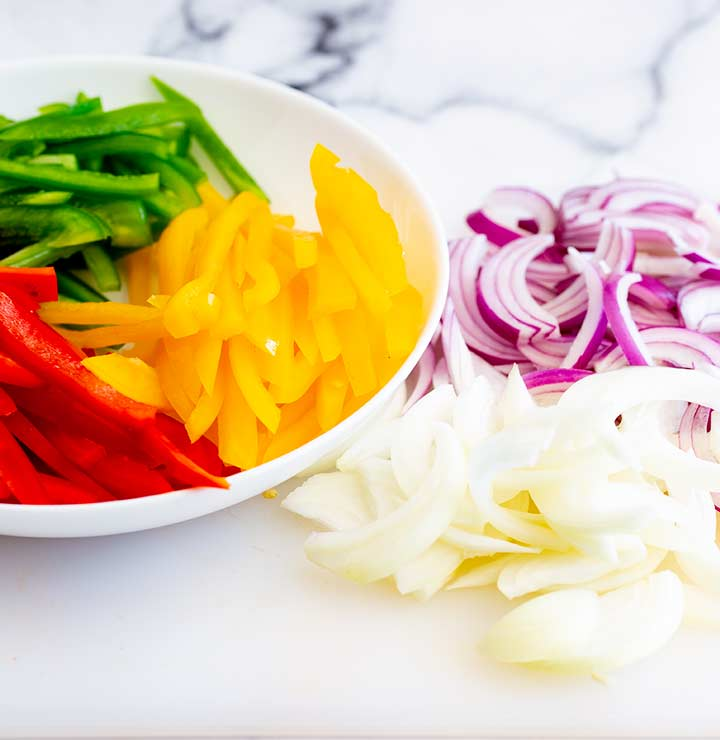 a bowl of sliced bell peppers with sliced onions next to it