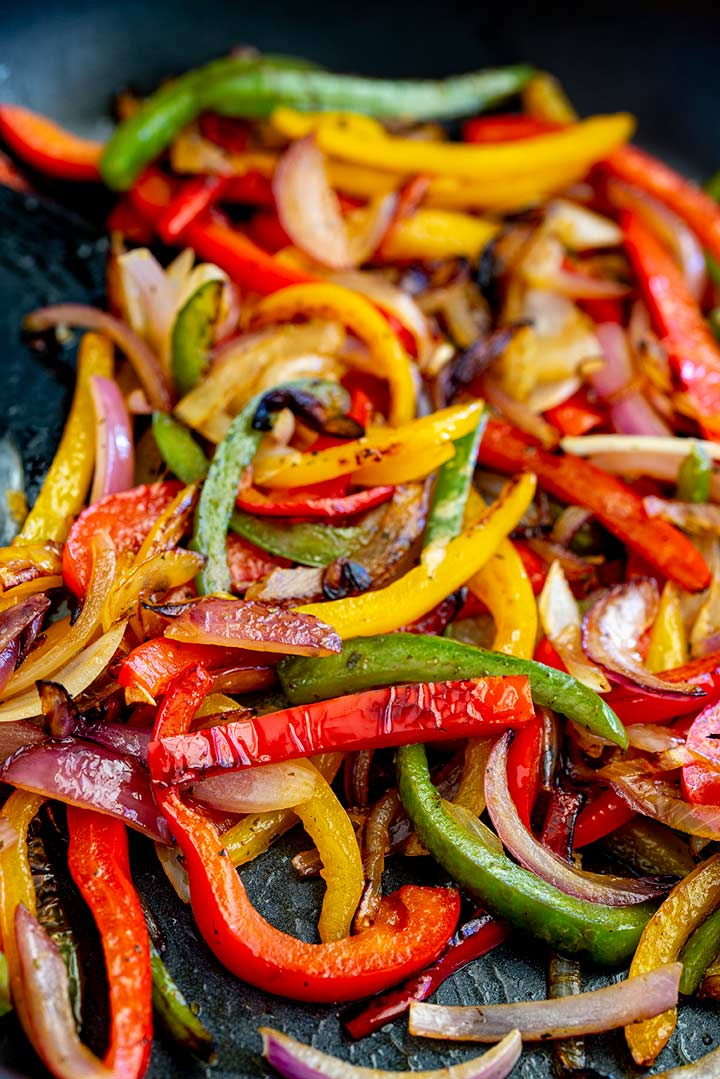 a black skillet filled with charred fajita veggies