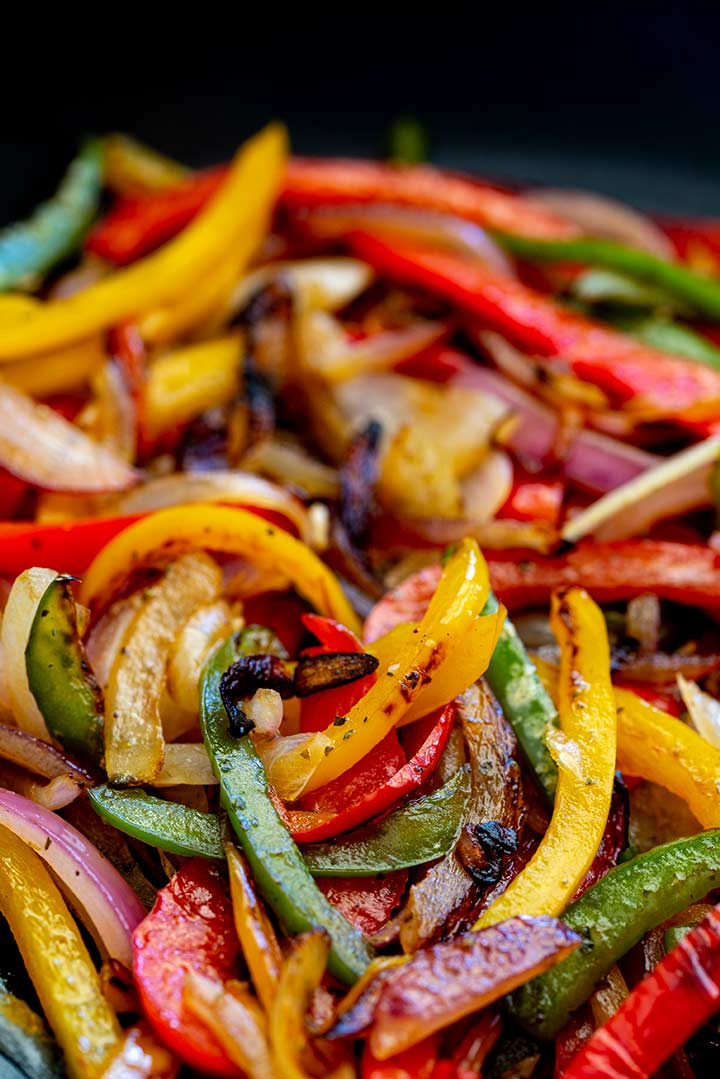cooked fajita vegetables in a black skillet
