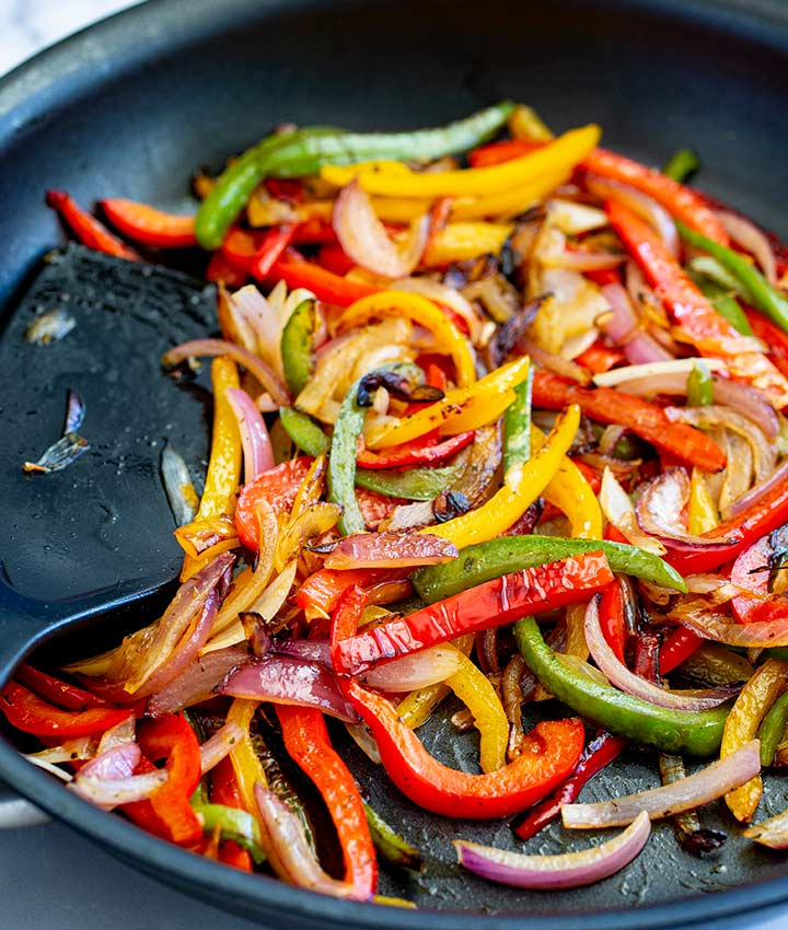 a black skillet with a spatula and charred bell peppers and onions
