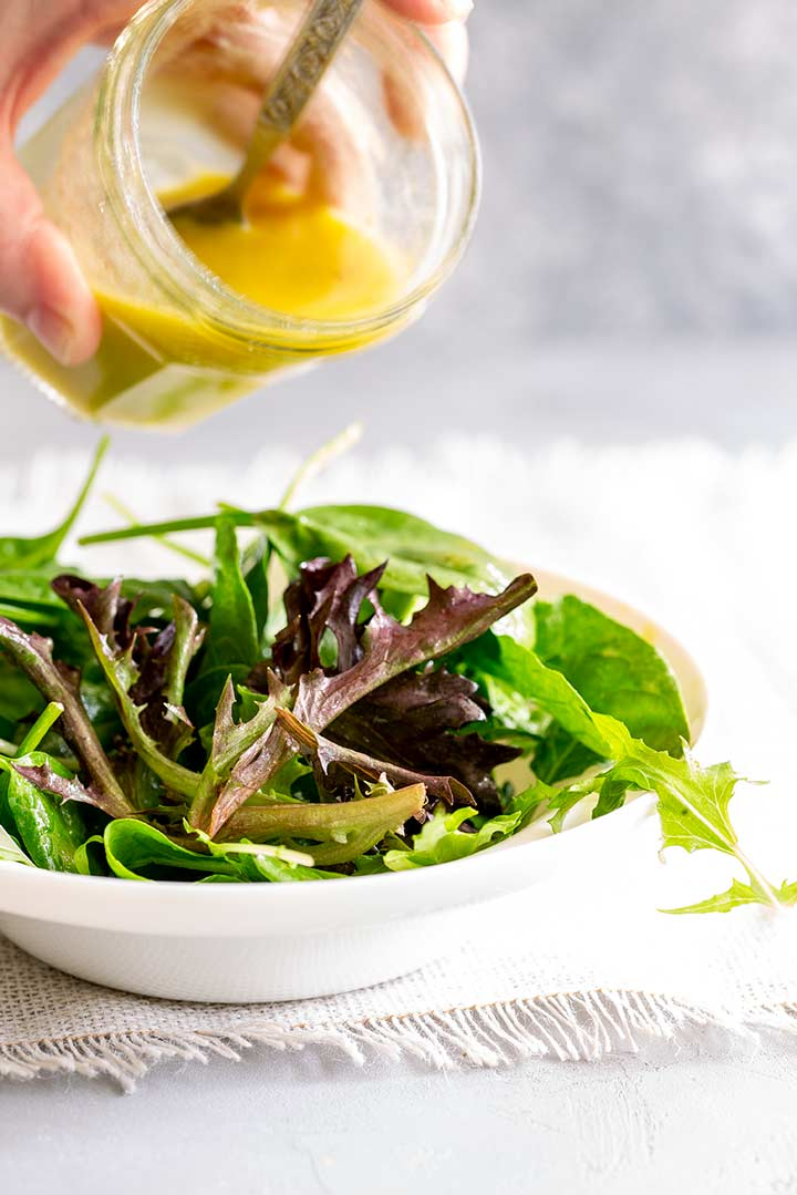 a glass jar of salad dressing above a bowl of mixed leaves