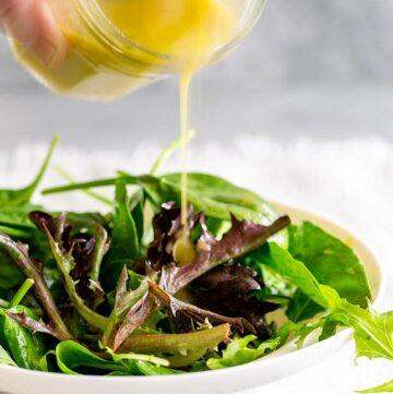 salad dressing being poured over salad leaves