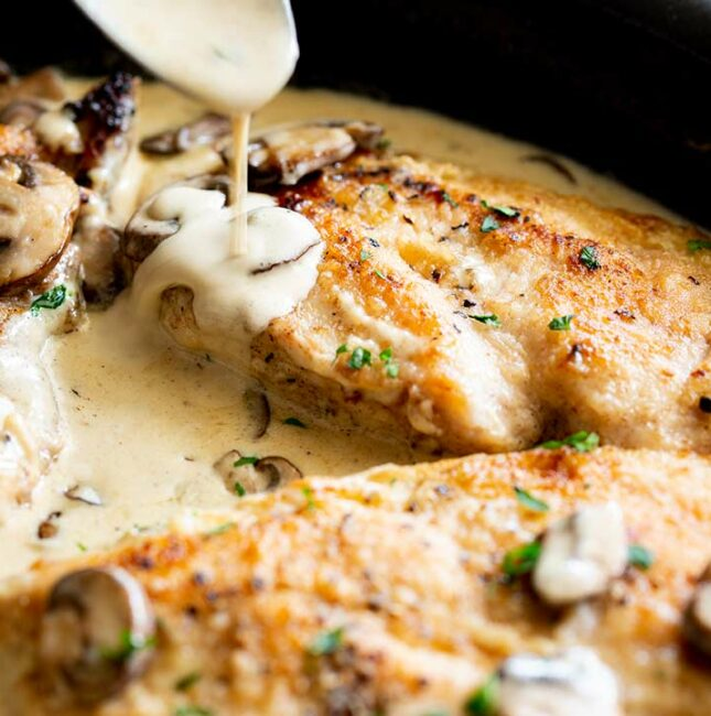 close up of creamy mushroom sauce drizzling over cooked chicken breasts