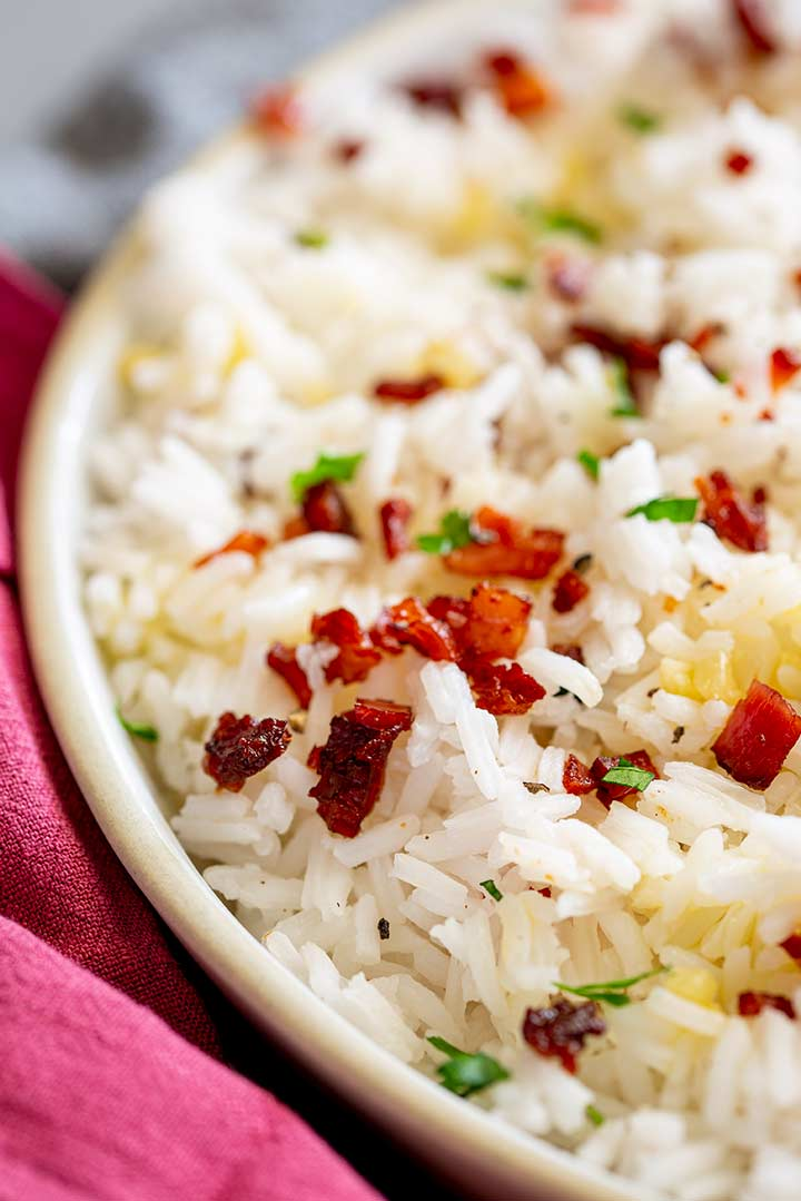 a earthen bowl filled with white rice topped with crispy bacon bits