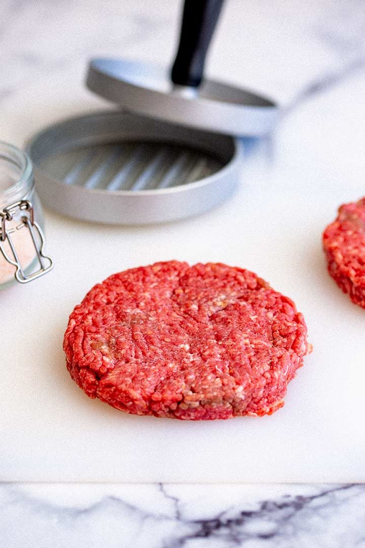 a raw burger patty in a white chopping board