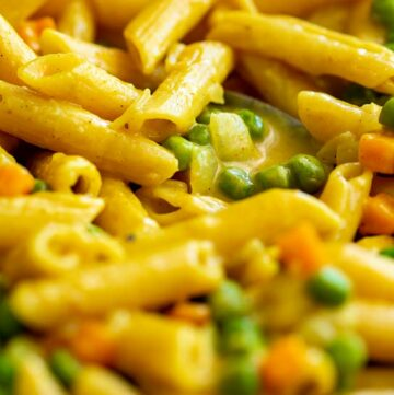close up of curried penne pasta with peas