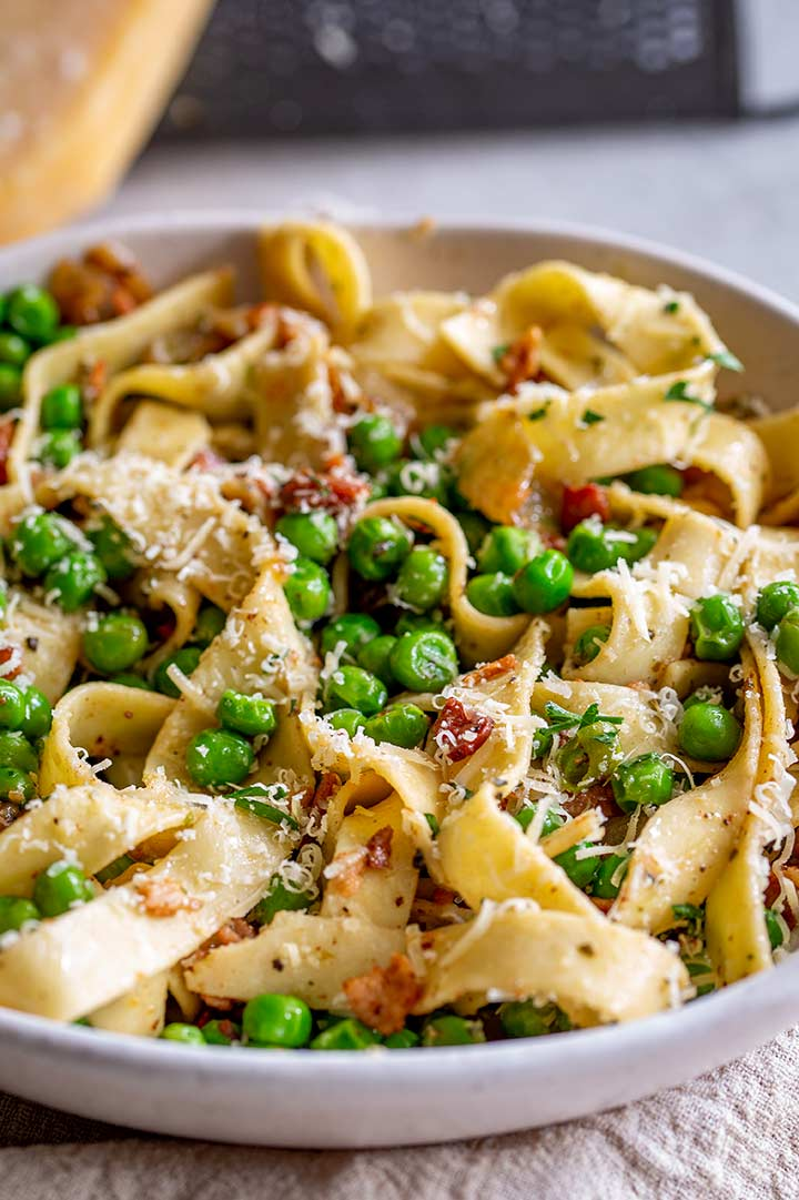 bacon and peas in a bowl of pappardelle