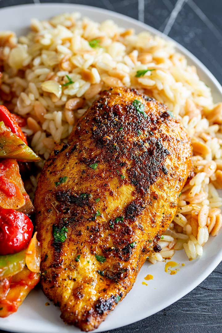 charred chicken breast on a bed of pilaf