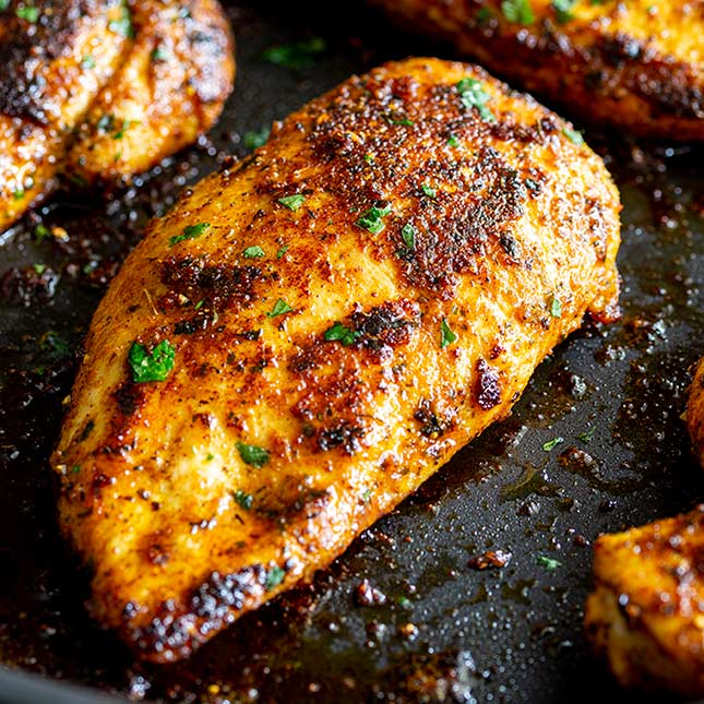 close up of a cooked chicken breast with Turkish spices on it