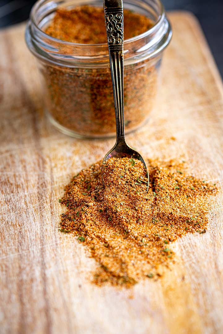 a spoon of spice mixture leaning against a glass jar
