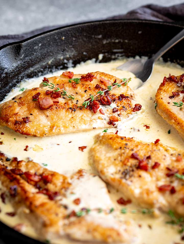 a cast iron skillet with chicken breasts and a cream sauce