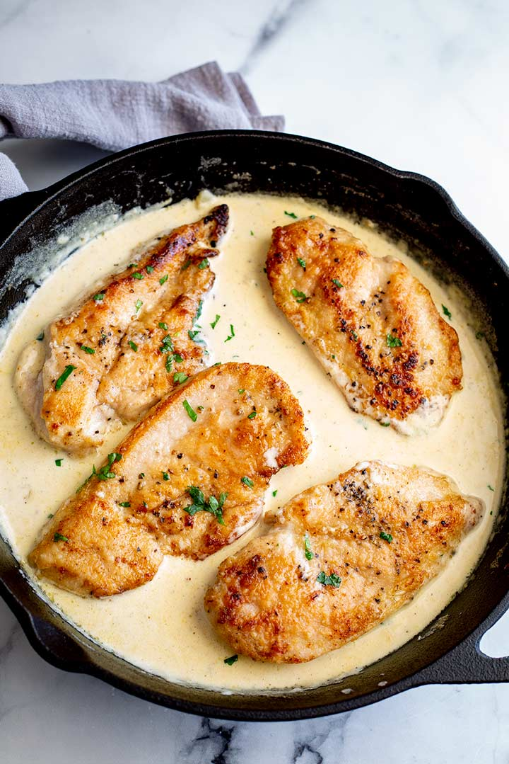 4 golden chicken breasts in a cast iron pan with a sauce