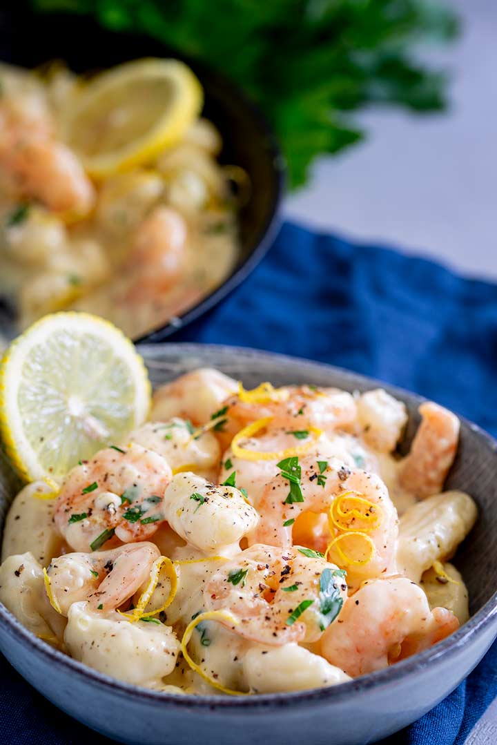 a grey bowl of gnocchi and shrimp with a skillet behind